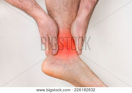 Man With Ankle Pain Holding His Aching Leg - Body Pain Concept
