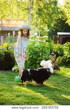 Happy Child Girl Playing With Her Spaniel Dog And Throwing Ball, Enjoying Sunny Summer Day In Garden
