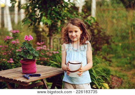 Happy Kid Girl Playing In Summer Garden, Holding Heranium Flower In Pot. Teaching Kids To Love Natur
