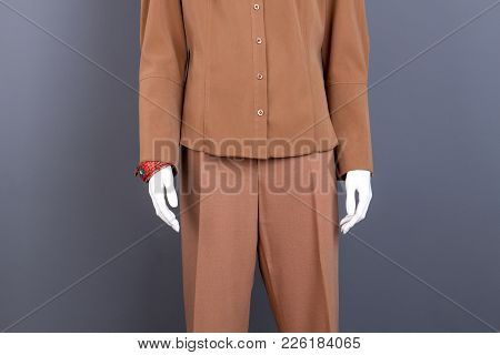 Female Mannequin In Formal Brown Apparel. Dummy In Female Office Blouse And Trousers, Grey Backgroun