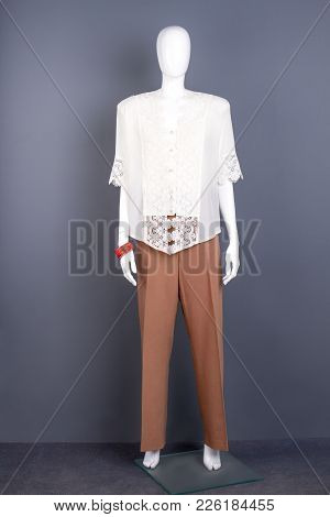 Female Mannequin In White Silk Blouse. Dummy Dressed In White Lace Blouse And Brown Trousers, Grey B