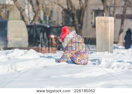 A Child Is Playing In The Snow. A Child Plays In Winter With A View From The Spen. The Child Plays I