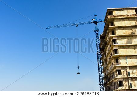 The Buildings Under Construction With The Active Crane Have A Blue Background And Sunlight. Industri