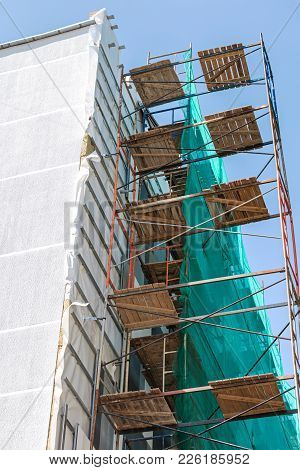 Building Exterior Renovation With Thermal Insulation Of Walls. Scaffolding On Construction Site.