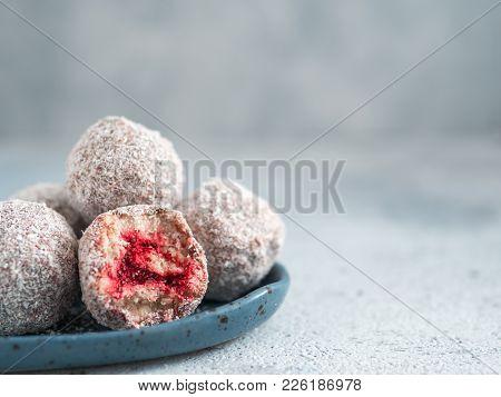 Raw Vegan Lamington Bliss Balls With Raspberries Chia Jam On Gray Background. No Baked Healthy Vegan
