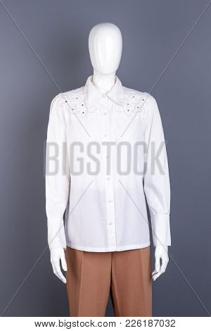 White Blouse With Rhinestones On Mannequin. Dummy In Female White Shirt And Brown Classic Trousers,