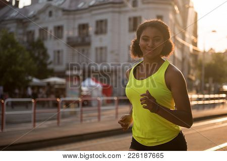 Jogger Woman Looking At Camera While Running