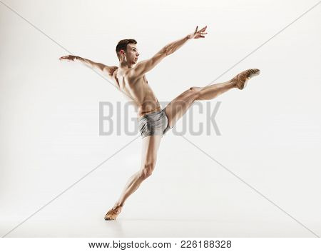 Athletic Ballet Dancer In A Perfect Shape Performing Isolated On The White Background. Studio Shot.
