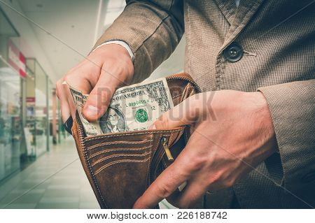 Man Holding Leather Wallet With Only One Dollar Inside In Shopping Centre - Retro Style