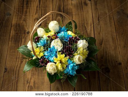 A Basket Diferent Flowers On A Wooden Background