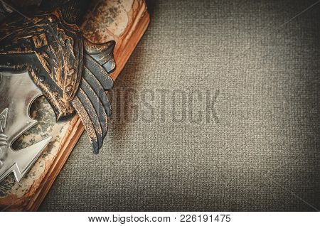 A Hilt Of A Sword Lies On The Old Book On Textile Background Copy Space