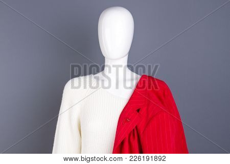 Female Mannequin With Clothes, Grey Background. White Knitted Sweater And Red Jacket For Women.