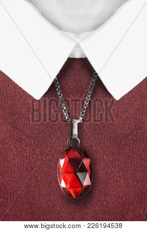 Red Faceted Gemstone Pendant Hanging Over Knitted Pullover With White Collar