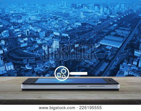 Seo Flat Icon On Modern Smart Phone Screen On Wooden Table Over City Tower, Street And Expressway, S