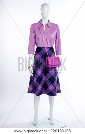 Female Mannequin In Blouse And Skirt. Purple Color Shirt, Skirt And Bag On Female Mannequin, White B