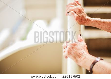 Elderly Woman's Hands Climbing Stair Using Handrail With Copy Space, White Background
