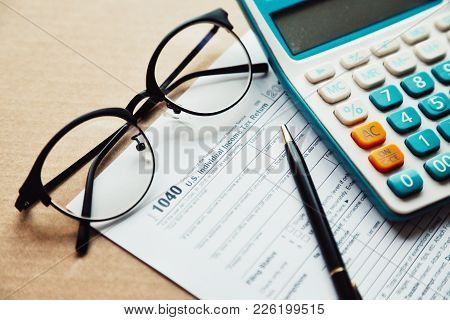 Close Up Income Tax Return Planning ,1040 Tax Form, With Calculator, Pen And Eye Glasses Place On Th
