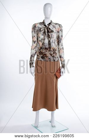 Chiffon Patterned Blouse And Brown Skirt. Female Mannequin In Skirt And Blouse On White Background.