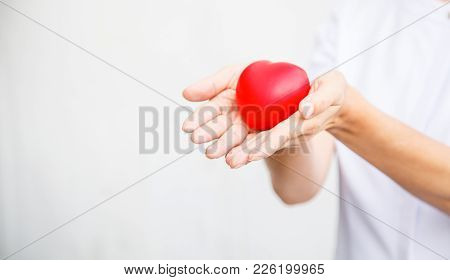 Selective Focus Of Red Heart Held By Female Nurse's Both Hand, Representing Giving All Effort To Del