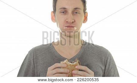 Young Man Eats A Burger. Concept Unhealthy Food.