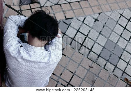 Aerial View Of Stressed Depressed Young Asian Business Man Suffering From Severe Depression.
