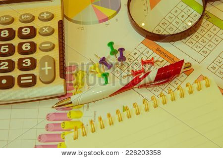 The Documents Painted Colorful Graphics. Above Lies The Pen And Calculator. Business Balance Sheet