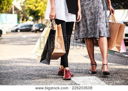 Female Ladies Carrying Colorful Shopping Bags In The Parking Lots Concept.