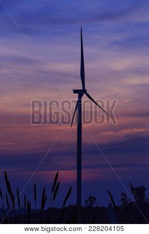 Silhouette Wind Turbine Farm Over Moutain Cloud In Blue Twilight Sky