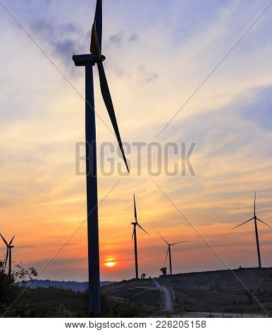 Silhouette Wind Turbine Farm Over Moutain With Orange Sunset And Cloud In Blue Twilight Sky