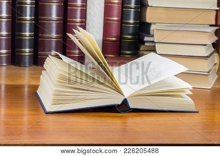Open Book With Blue Cover On A Wooden Table At Selective Focus With Blurred Text Against Of The Othe