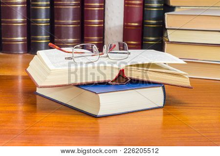 Classic Mens Eyeglasses Lying  On The Open Book On A Wooden Table Closeup Against Of The Other Books