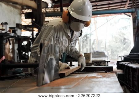 Soft Focus Of Professional Young Worker In White Uniform And Safety Equipment Cutting A Piece Of Woo