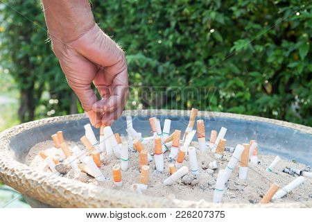 Old Man's Hand Stop Smoking On Ashtray, Close Up Shot With Cigarettes On Ashtray