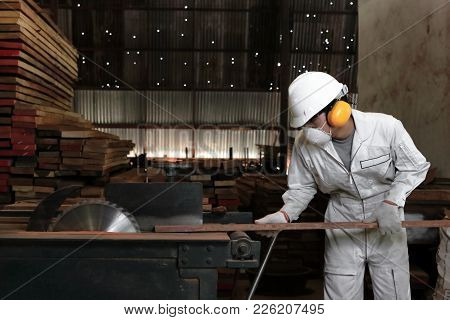 Professional Young Carpenter With Safety Equipment Cutting A Piece Of Wood On Table Saw Machine In C