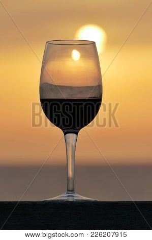 Wine Glass On Table With The Sun Reflecting Behind It, At Sunset