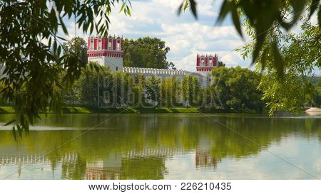 View From Behind The Trees At Novodevichy Convent. Reflection Of The Monastery In The Pond. Moscow,