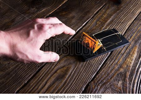 Man's Hand Stretches For A Banknote Which Is Bait In A Mousetrap.