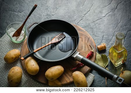 Cast-iron Frying Pan And Potatoes. Cooking Fried Food. Dark Stone Background. Copy Space.