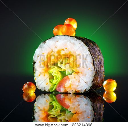 Sushi roll japanese food over black background. Sushi roll with tuna, vegetables, flying fish roe and caviar closeup. Japan restaurant menu.