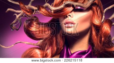 Red Hair. Fashion Model sexy Woman Portrait with Long Curly Red Hair on Wood Branches. Hair Extensions, Luxury high fashion style, make-up. Beauty face makeup