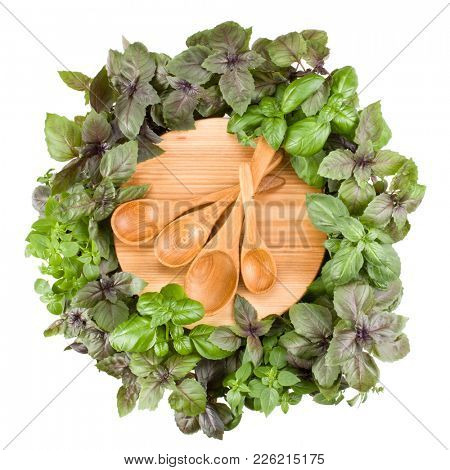 Round wooden cutting board with spoons. Various sweet basil herb leaves edged.. Healthy food concept. Top view.