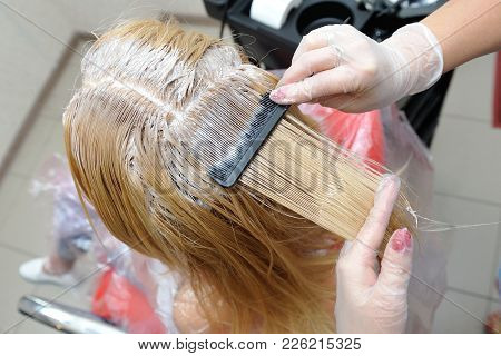 The Hairdresser Smears The Paint On His Hair With A Comb, For Coloring The Blonde.
