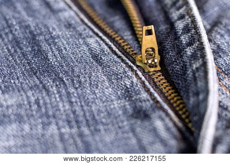 Golden Brass Zipper On Blue Jeans. Selective Focus. The Zipper Is Device Consisting Of Two Flexible