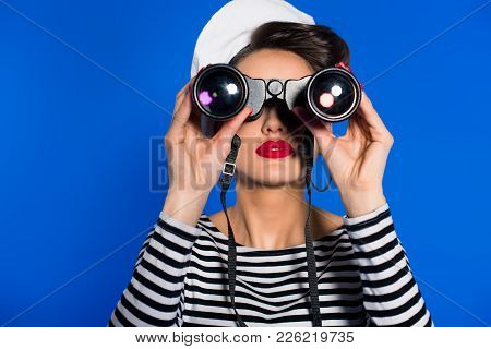 Obscured View Of Attractive Young Woman In Retro Clothing With Binoculars Isolated On Blue
