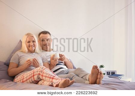 Senior couple drinking coffee on bed together