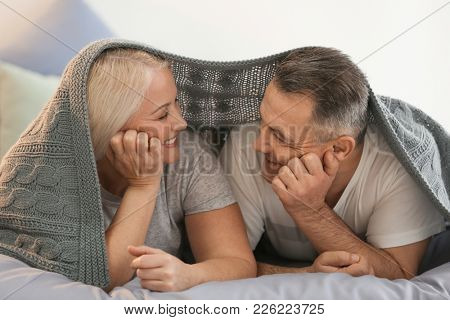 Senior couple under plaid on bed together