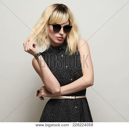 Blonde Girl In Elegant Dress And Trendy Sunglasses. Fashion Young Woman In Stylish Outfit. Portrait
