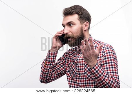 Heated Conversation. Handsome Bearded Man In A Checked Shirt Talking On The Phone Emotionally And Ge
