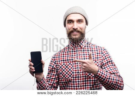 Upbeat Listener. Joyful Young Man In A Grey Beanie Listening To The Music In Headphones And Pointing