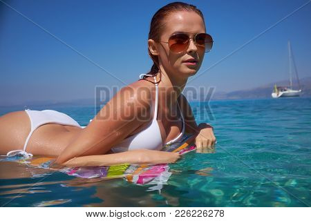 girl on the beach against a blue sunny sky. Holds a pink inflatable mattress, sunglasses, wet tanned skin. Rest, south, resort, beach. Sunny day.
